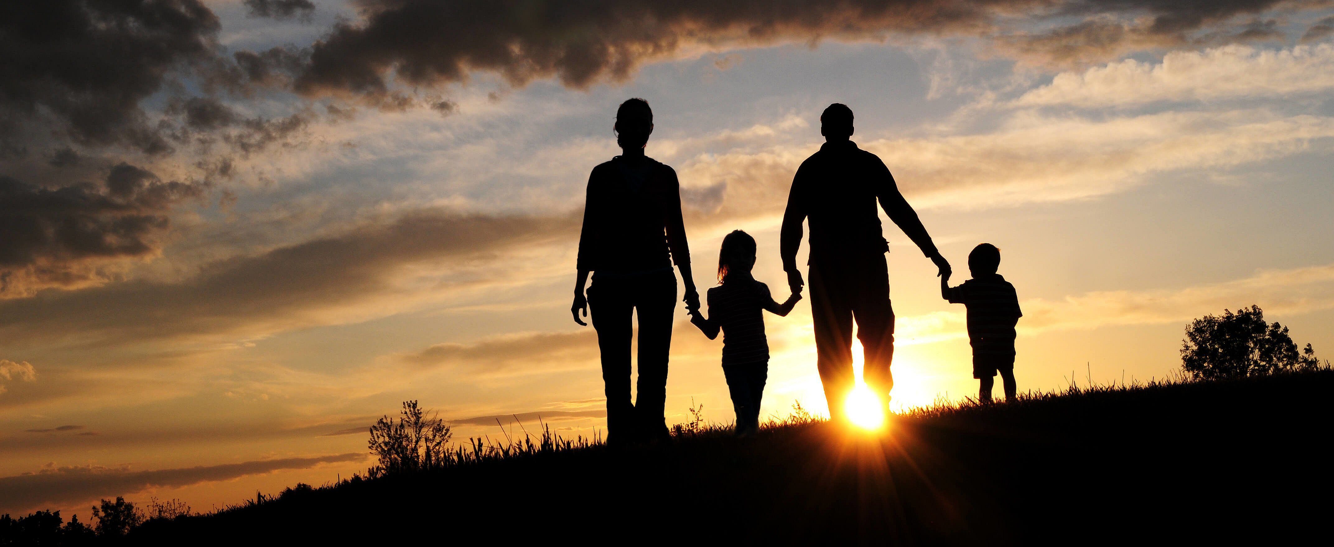 A silhouette of a family walking at sunset