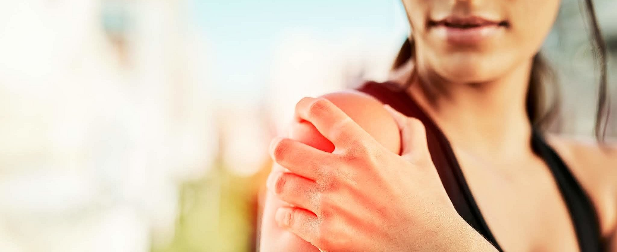 Closeup shot of a sporty young woman holding her shoulder in pain while exercising outdoors